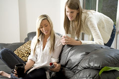 Two friends relaxing on sofa Stock Photos