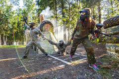 Two friends rescue their friend from coming locomotive. In paintball game Stock Photo