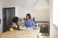 Two friends researching recipes at the kitchen table stock image