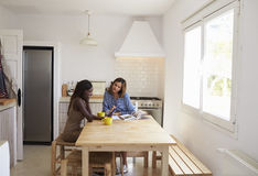 Two friends researching recipies at the kitchen table, full length Stock Images