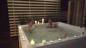 Two friends rest after a hard day in the jacuzzi with bubbles in the spa center. Two friends share their impressions of staying in an expensive spa center stock video