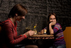Two friends in a restaurant. Two girls tittle-tattle at the table in a restaurant Royalty Free Stock Photos