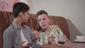 Two friends resting in the restaurant sitting on the leather sofa talking and laughing. The man using the cellphone. Portrait of two male friends resting in the stock video