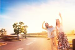 Urban hipster girls hitchhiking on roadside. Two friends on a road trip, hipster girls hitchhiking on roadside of highway royalty free stock photography