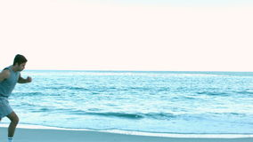 Two friends running on the beach stock footage