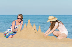 Two friends with sand castle Stock Photography