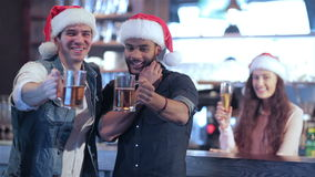 Two friends in Santa hats and the girl behind the. Cheerful company of guys and girl celebrating at the bar. The company has a rest after work. Cheerful company stock video