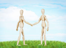 Two friends shake hands to each other. Abstract image with wooden puppets Stock Images