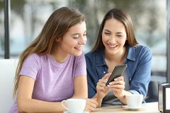Two friends sharing on line content in a smart phone in a bar Stock Photos