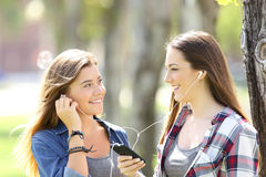 Two friends sharing on line music outdoors Stock Images