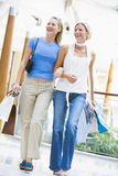 Two friends shopping in mall. Carrying bags Royalty Free Stock Photo