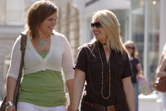 Two friends on a shopping trip. Friends walking down a busy shopping street on a sunny afternoon royalty free stock photography