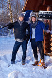 Two friends shoveling snow from the yard in winter cottage.  Royalty Free Stock Images