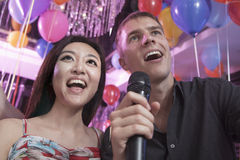Two friends singing into a microphone together in a nightclub for karaoke Royalty Free Stock Images