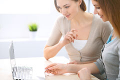 Two friends or sisters making online shopping by credit card. Friendship, family business or internet surfing concept.  Royalty Free Stock Images
