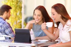 Two friends or sisters watching videos in a tablet. In a coffee shop terrace Royalty Free Stock Photography