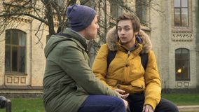 Two friends sit on bench near university. Two students walks in park near the university. Friends are discussing some educational material. Young people talks stock footage