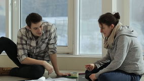 Two friends sit near big window and discuss plan of building. Man is dressed in checkered shirt and black jeans, he wears yellow massive boots on his feet stock video