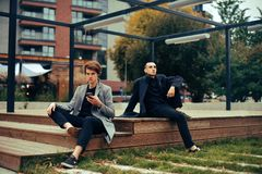 Two friends sit in the park on a bench. Friendship. Two fashion men in coats . royalty free stock photo