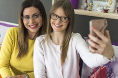 Two friends sit and photograph themselves with a smartphone. Two adult smiling girls with glasses take pictures of themselves with a smartphone Royalty Free Stock Photography