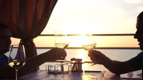 Two friends sit by the sea at sunset with glasses of wine in hands. HD, 1920x1080. slow motion stock video