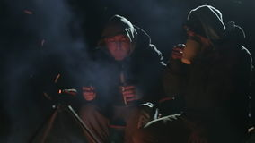 Two friends sits next to bonfire in wood at night, talking and drinking tea. Two friends in warm clothes sits next to bonfire in wood at night, talking and stock video footage