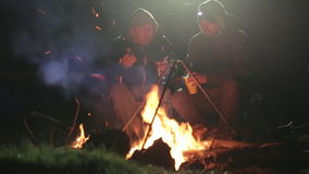 Two friends sits next to bonfire in wood at night, talking and drinking tea. Two friends in warm clothes sits next to bonfire in wood at night, talking and stock footage