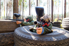 Two friends sitting in big truck tires with paintball guns Stock Photos