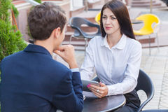 Two friends sitting in cafe and discussing their business. Two friends sitting outdoor in cafe thinking, looking at tablet and discussing their business Royalty Free Stock Photos