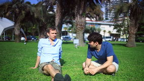 Two friends are sitting in a green clearing in the middle of the city and talking, homosexuals are resting.  stock footage
