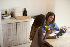 Two friends sitting in kitchen, using tablet and reading Stock Images