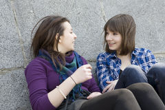Two friends sitting near stone wall. Stock Photo