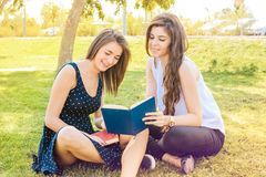 Two friends sitting in a park listening to music Royalty Free Stock Photos