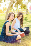 Two friends sitting in a park reading a book Royalty Free Stock Images