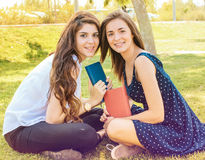 Two friends sitting in a park reading a book Stock Image