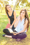 Two friends sitting in a park reading a book Stock Photography