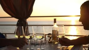 Two friends are sitting in a restaurant by the water near the sea at sunset, drinking wine. HD, 1920x1080. slow motion stock video footage