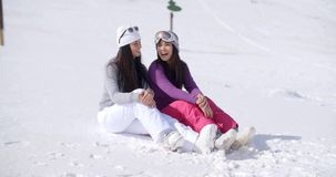 Two Friends Sitting Together on Sunny Ski Hill stock video