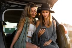 Best friens watching something on the phone. Two friends sitting in the trunk of a car while watching something on the phone Stock Photography