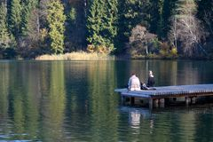 Two friends sitting on a wooden pier on a lake enjoying and relaxing royalty free stock photography