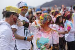 Geoje, SOUTH KOREA - MARCH 2018: Holi festival. Two friends smearing colors on face stock photography