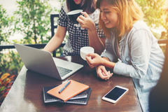 Two friends smiley enjoying working together in a coffee shop. Stock Images