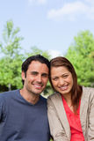 Two friends smiling as the look ahead while leaning against each Royalty Free Stock Photography