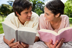 Two friends smiling at each other while reading on a blanket Royalty Free Stock Image