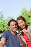 Two friends smiling happily as the look at the photo collection Stock Images