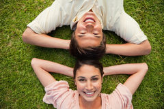 Two friends smiling while lying head to head Royalty Free Stock Photography