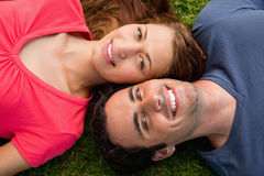 Two friends smiling while lying head to shoulder. In a park Royalty Free Stock Photos
