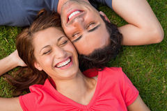 Two friends smiling while lying head to shoulder with an arm beh Stock Image
