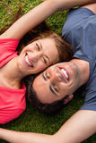 Two friends smiling while lying head to shoulder with an arm out Royalty Free Stock Images