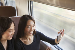 Two Friends Smiling and Taking a Picture Out the Train Window Stock Photos